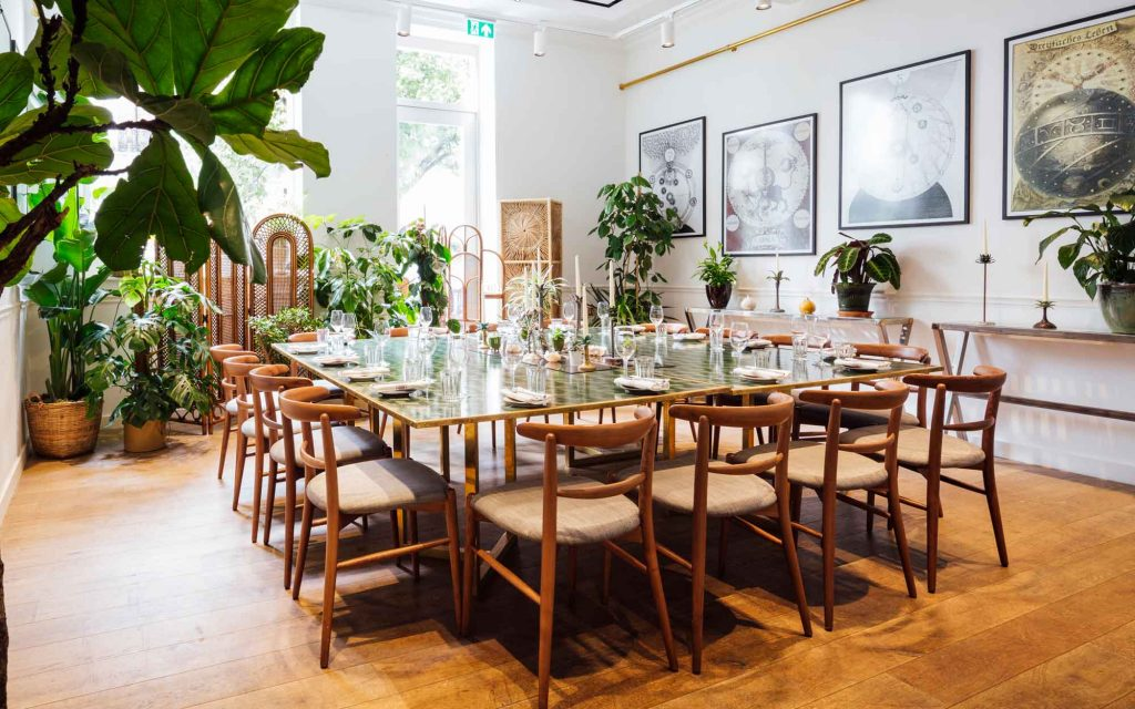 The lush green and bright private dining room at Farmacy on Westbourne Grove in London.